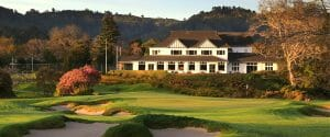 The 18th green sits below a dusk-covered clubhouse at Royal Wellington Golf Club