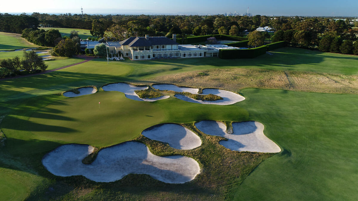 The Royal Melbourne clubhouse overlooks a large green and bunkers on the eighteenth hole