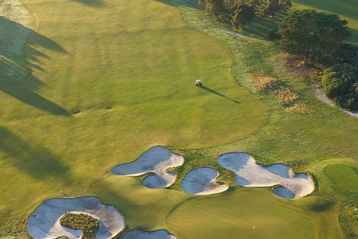 The setting sun casts a long shadow over the Royal Melbourne Golf Course