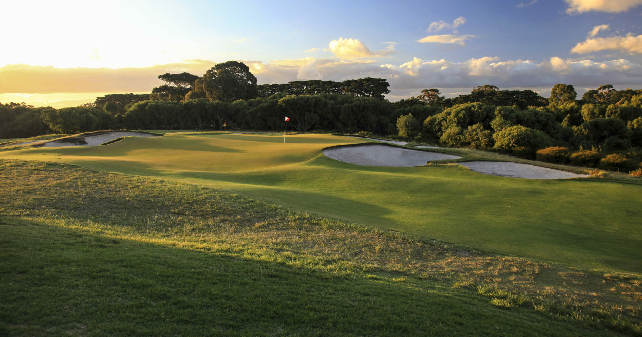 Setting sun casts golden light over the fifth green at Royal Melbourne