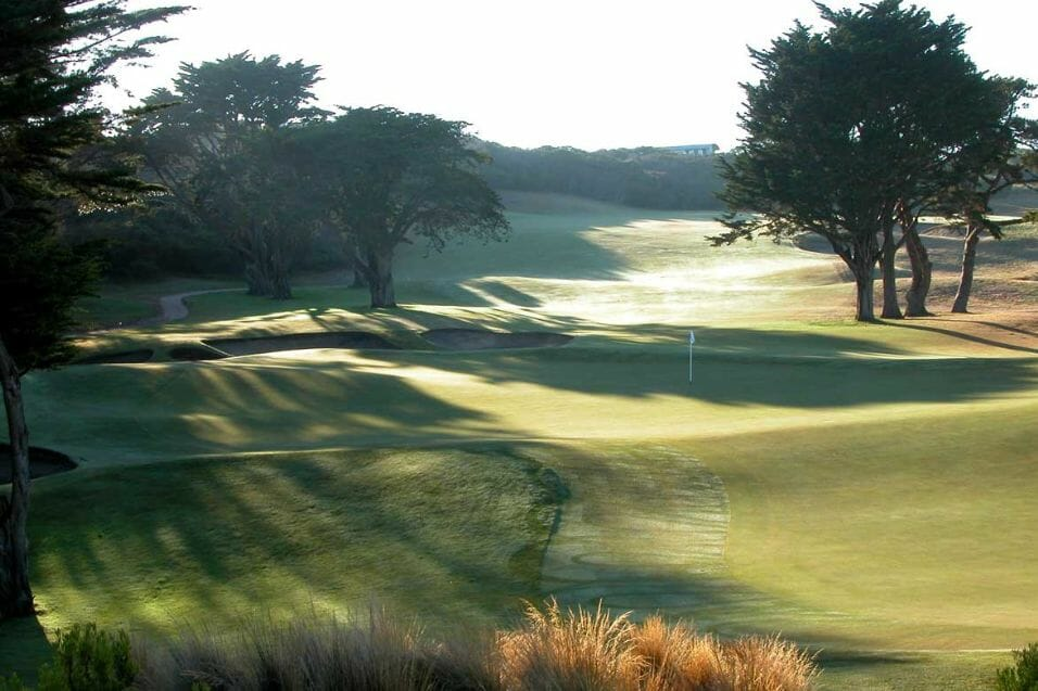 Overlooking pine trees leading to a green on The Old Course at The National Golf Club