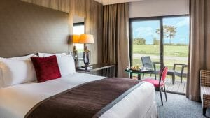Double bed and balcony adorn a golf view room at the resort
