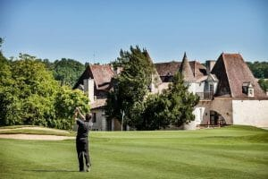 Golfer swings in front of the Chateaux de Vigiers building