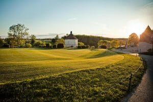 Golden light from sunset shines on the practice putting green at Chateaux de Vigiers