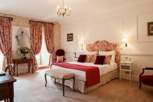 Old-style designed bedroom with warm red tones at Chateaux de Vigiers
