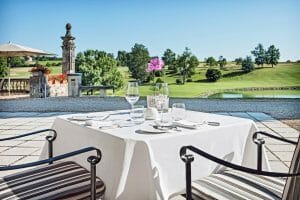 Outdoor dining on a terrace overlooks the golf course and stunning scenery