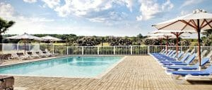 Outdoor pool is flanked by sun lounges at Chateaux des Vigiers Resort
