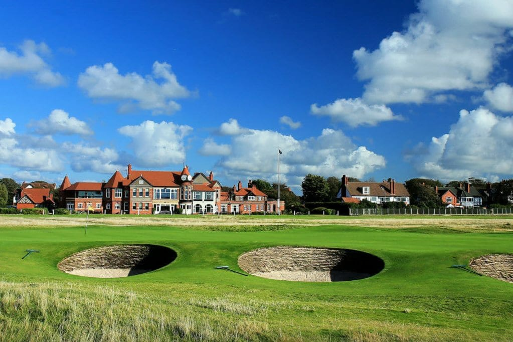 Landscape view of the Royal Liverpool clubhouse and nearby pot bunkers