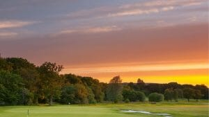 Setting sun casts golden light over the golf course and countryside