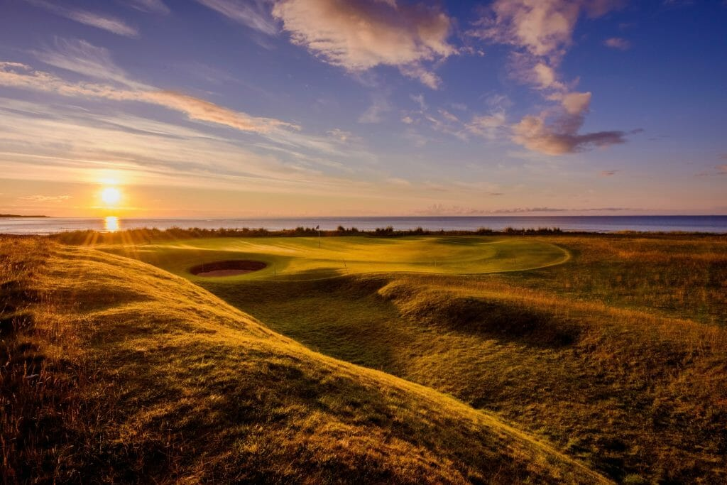 Golden light of sunset shines over the Brora Golf Club in Scotland