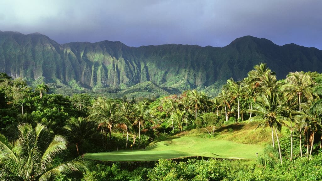 An island green is dwarfed by Hawaiian mountains and vegetation
