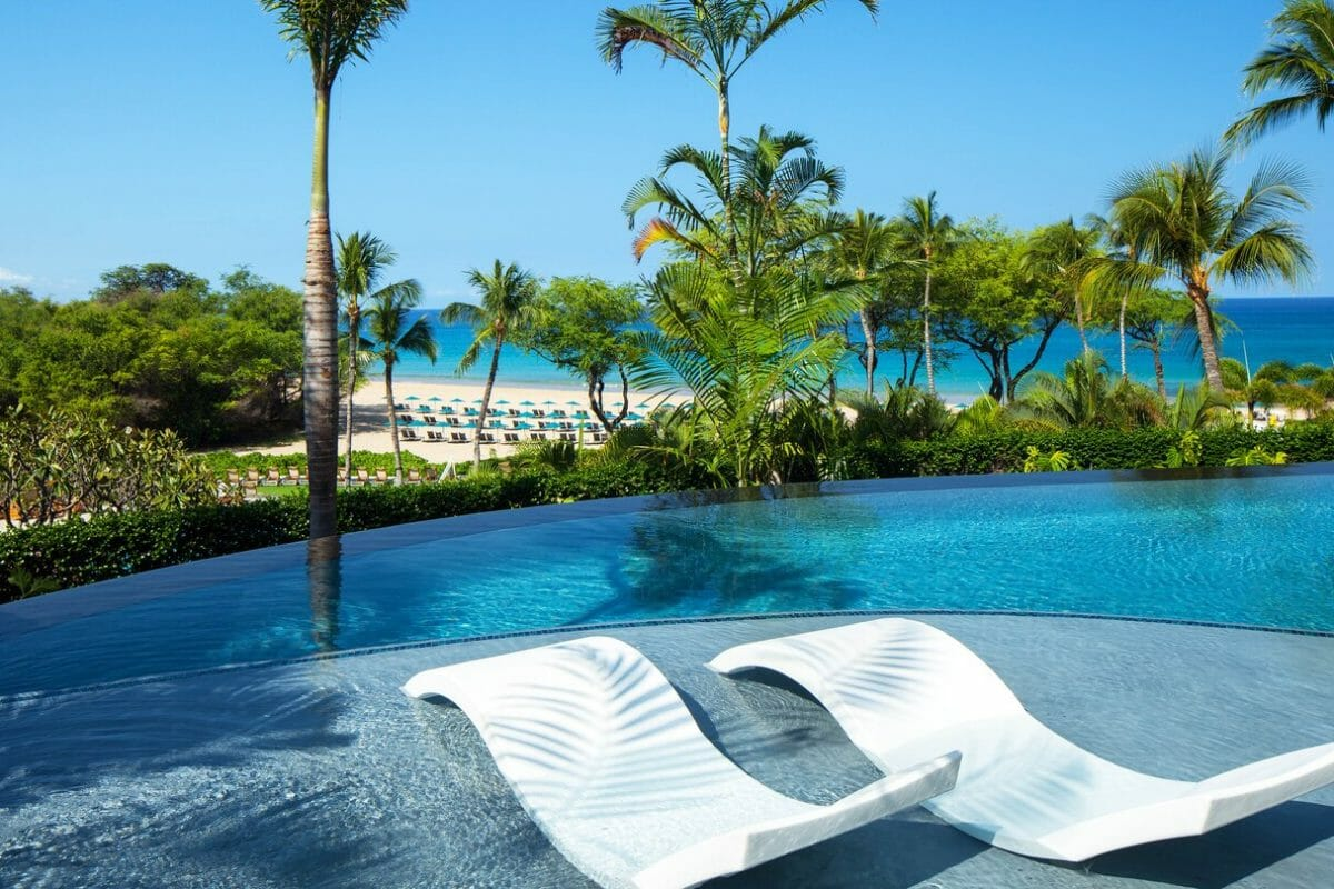 Two reclining sun lounges lie in the shallows of a pool at Westin Hapuna Beach Resort