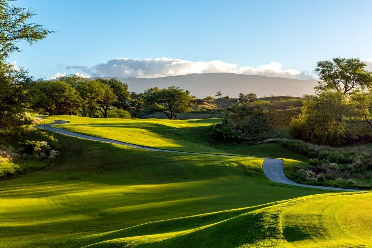 Golden light of sunset shines on the golf course at Hapuna Beach