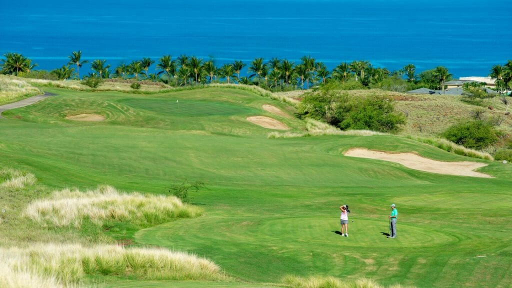 Two golfers stand on a tee overlooking the Pacific Ocean