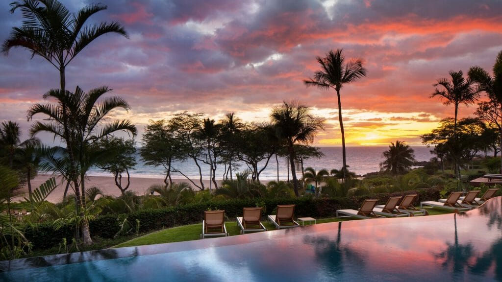 Golden light of the setting sun overlooks an infinity pool at the Westin Hapuna Beach Resort