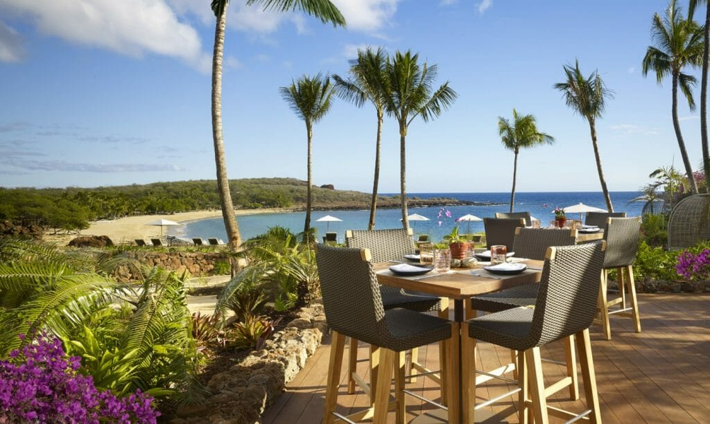 A dining table overlooks a private beach at Lanai Four Seasons Resort