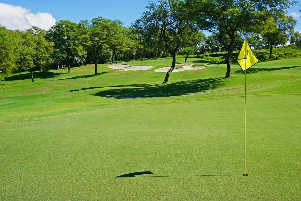 A yellow golf flag stands in the fourteenth green of the Emerald Course at Wailea