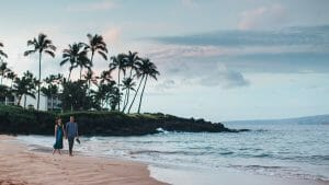 A couple walks on the private beach in front of Wailea Beach Resort