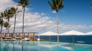 An infinity pool overlooks the Pacific Ocean with cabanas
