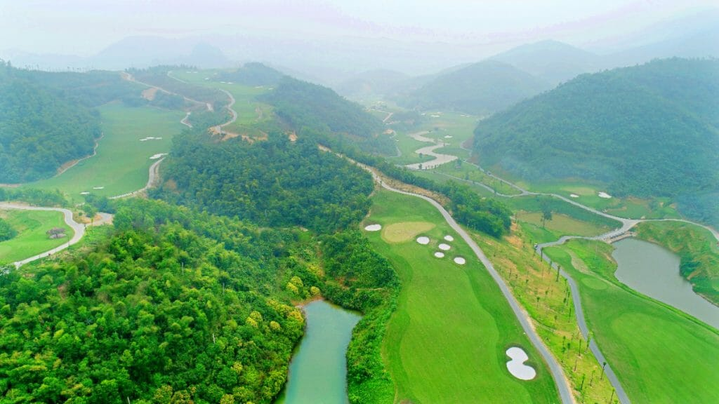 Aerial view of golf holes winding through a valley