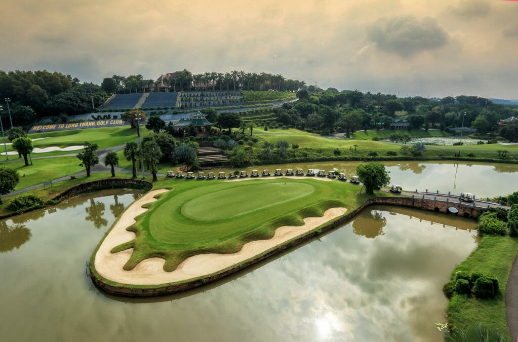 A large green is manicured around a bunker and lake at Long Thanh